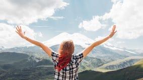 站立在峭壁的年轻女人徒步旅行者和享用看法山在夏天,背面图 免版税库存图片