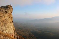 站立在峭壁的边缘和享用谷的女孩远足者竞争 库存照片