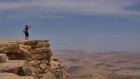 站立在峭壁边缘和拍沙漠的全景照片的他的电话的年轻人 免版税库存照片