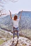 站立在峭壁边缘和握她的手的活跃妇女悬而未决 阿迪格共和国共和国山在俄罗斯 库存照片