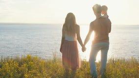 站立在峭壁边缘的愉快的家庭反对海和日落, 影视素材