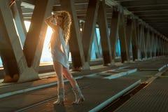 站立在工业桥梁locati的美丽的卷曲白肤金发的妇女 库存图片