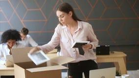 站立在工作书桌附近的被射击的年轻人生气妇女包装盒