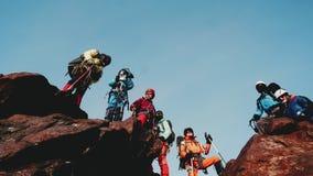 站立在巨大的岩石,一个被协调的小组登山人对他的在竞选的成就满意 股票录像