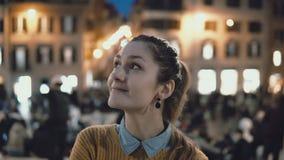 站立在市中心的年轻美丽的妇女画象在晚上 学生女孩看照相机,微笑 免版税库存图片