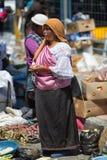 站立在市场上的盖丘亚族人的妇女在Otavalo厄瓜多尔 免版税库存照片