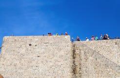 站立在市的老墙壁上的游人DUrovnik,达尔马提亚,克罗地亚 图库摄影