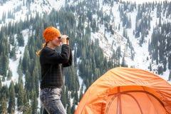 站立在帐篷附近和看通过双筒望远镜的美丽的旅游女孩积雪覆盖的山 免版税库存图片