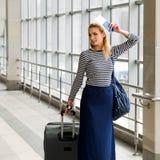 站立在带着一个大手提箱的与票的驻地和护照的一件镶边女衬衫的旅游白肤金发的女孩 免版税库存图片