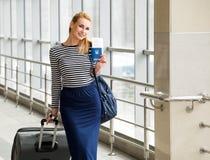 站立在带着一个大手提箱的与票的驻地和护照的一件镶边女衬衫的旅游白肤金发的女孩 库存照片