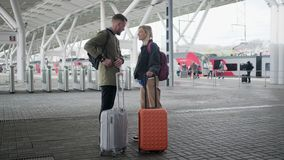站立在带着手提箱的平台的旅客愉快的夫妇在离开前 影视素材