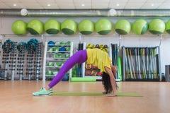 站立在席子的螃蟹姿势的少妇在健身演播室,当实践的瑜伽行使时 库存照片
