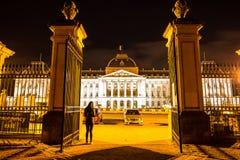 站立在庄严比利时联邦议会前面门的亚裔妇女在国家的宫殿在晚上在布鲁塞尔 免版税库存图片