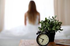 站立在床头柜上的闹钟在坐在背景中的床上已经敲响清早叫醒妇女 免版税库存图片