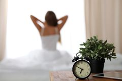 站立在床头柜上的闹钟在坐在背景中的床上已经敲响清早叫醒妇女 免版税图库摄影