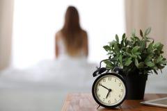 站立在床头柜上的闹钟在坐在背景中的床上已经敲响清早叫醒妇女 免版税库存照片