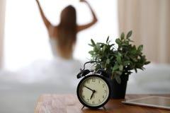 站立在床头柜上的闹钟在坐在背景中的床上已经敲响清早叫醒妇女 库存图片