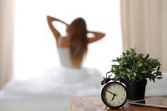 站立在床头柜上的闹钟在床上在背景中已经敲响清早叫醒妇女舒展 免版税库存图片