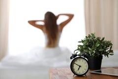 站立在床头柜上的闹钟在床上在背景中已经敲响清早叫醒妇女舒展 免版税图库摄影