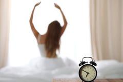 站立在床头柜上的闹钟在床上在背景中已经敲响清早叫醒妇女舒展 库存照片