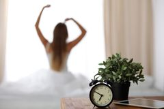 站立在床头柜上的闹钟在床上在背景中已经敲响清早叫醒妇女舒展 图库摄影