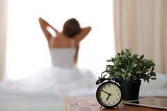 站立在床头柜上的闹钟在床上在背景中已经敲响清早叫醒妇女舒展 库存图片