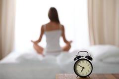站立在床头柜上的闹钟已经敲响清早醒 妇女在床上做瑜伽在背景中 库存照片