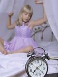 站立在床头柜上的闹钟 醒一个睡着的女孩舒展在床上在背景中 免版税图库摄影