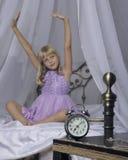 站立在床头柜上的闹钟 醒一个睡着的女孩舒展在床上在背景中 免版税库存照片