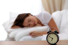站立在床头柜上的闹钟在床上已经敲响清早叫醒妇女睡觉在背景中的 免版税库存图片