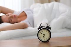 站立在床头柜上的闹钟在床上已经敲响清早叫醒妇女睡觉在背景中的 库存图片