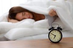 站立在床头柜上的闹钟在床上已经敲响清早叫醒妇女睡觉在背景中的 库存照片