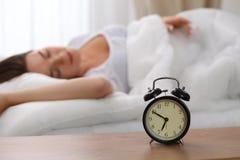站立在床头柜上的闹钟在床上已经敲响清早叫醒妇女睡觉在背景中的 免版税库存照片