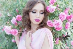 站立在庭院玫瑰的一件桃红色礼服的美丽的性感的女孩在与一柔和的构成和明亮的puf的一个晴朗的明亮的夏日 库存图片