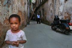 站立在庭院里一个老被毁坏的房子的小孩 免版税图库摄影