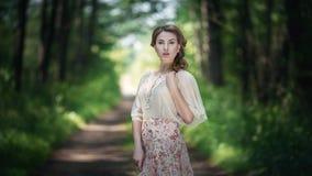 站立在庭院里的减速火箭的样式礼服的沉思美丽的女孩在篱芭附近 特写镜头表面纵向妇女 她是老师 库存照片