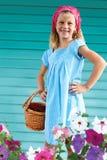 站立在庭院里的逗人喜爱的小女孩包围由花 免版税库存照片