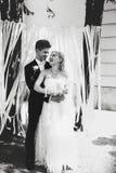 站立在庭院里的黑白微笑的新婚佳偶 免版税库存照片