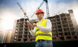 站立在建筑工地和使用数字式片剂的男性建筑工程师画象  库存图片