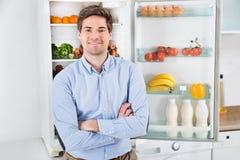 站立在开放冰箱前面的人 库存图片