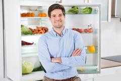 站立在开放冰箱前面的人 库存照片