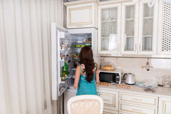 站立在开放冰箱前面的妇女 库存图片