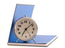 站立在开放书的闹钟 免版税图库摄影