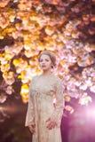 站立在开花的树的美丽的少妇在庭院里 库存图片
