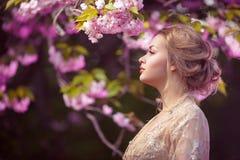 站立在开花的树的美丽的性感的成人女孩在庭院里 库存照片