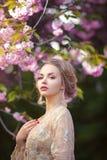 站立在开花的树的美丽的性感的成人女孩在庭院里 免版税库存照片