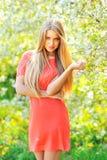站立在开花的树附近的美丽的年轻白肤金发的妇女 库存图片