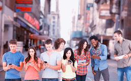 站立在彼此旁边和发短信在他们的电话的四个人的综合图象 免版税图库摄影