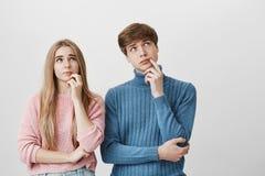站立在彼此附近的兄弟和姐妹有设法沉思的表示发现解答,向上看 两 库存照片