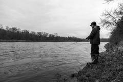 站立在快速流动的河河岸的坚固性户外渔夫  免版税库存图片